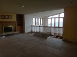 Living room without hardwood floors and carpet, damage to the ceiling and lower walls.