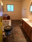 The master bathroom is still missing most functional appliances, but the floor is in.
