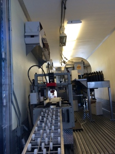 Looking into the back of the trailer: the beginning of the bottling line is at the right, bottles are cased and sealed before coming down the conveyor for stacking.