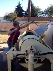 #8: Me cleaning the outside equipment (the slide and press) to be sure it is ready to take the fruit.