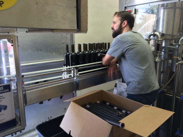 Capsule or screwcap placement on the bottling line.