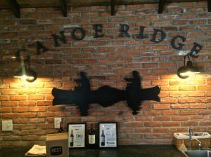 Canoe Ridge Vineyard logo on brick wall of the tasting room.