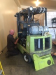 Forklift repairman putting a forklift back together.