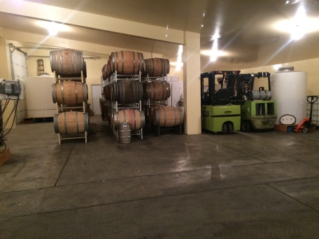 Stacked barrels of red wine and forklifts.