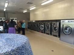 Industrial washers and dryers, with commercial circular clothes racks to hang clothes outfit this colony's laundry room.