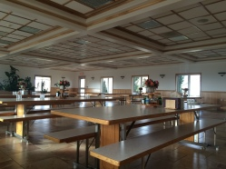 Parallel rows of tables, one for the men and one for the women, in the community dining hall.
