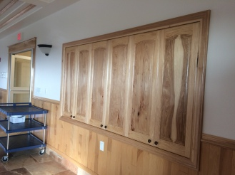 Handmade doors access the dishes and glassware to set the tables in the dining room.