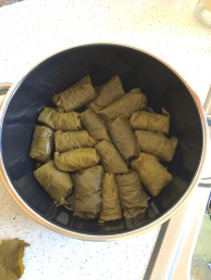 Place the dolma rolls in layers in the oiled pot, seam side down.