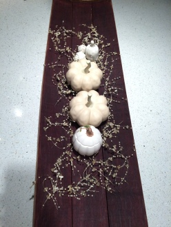 white pumpkins on barrel stave board