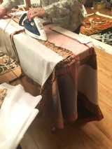 Ironing seams during quilt making.